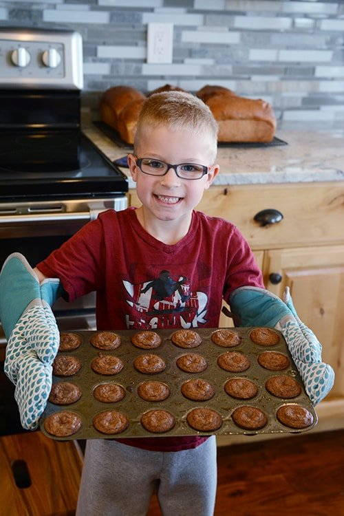 Little boy holding a pan of cooked muffins.