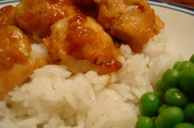 sticky honey glazed chicken, white rice, and green peas on a plate