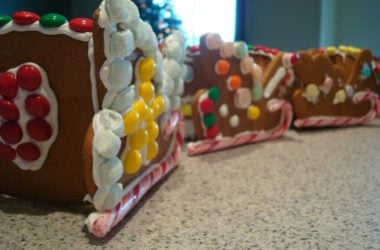 three gingerbread sleds decorated with frosting and candy in a line on a countertop