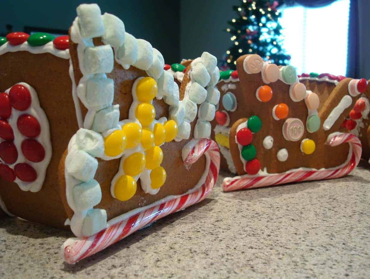 two gingerbread sleds decorated with candy canes and candy on a countertop