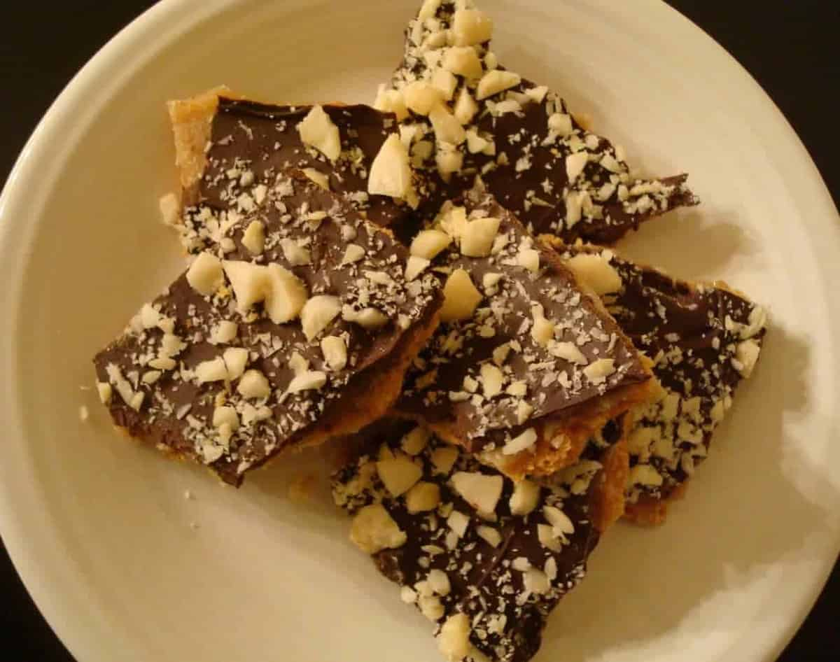 chunks of chocolate caramel toffee topped with crushed macadamia nuts on a white plate
