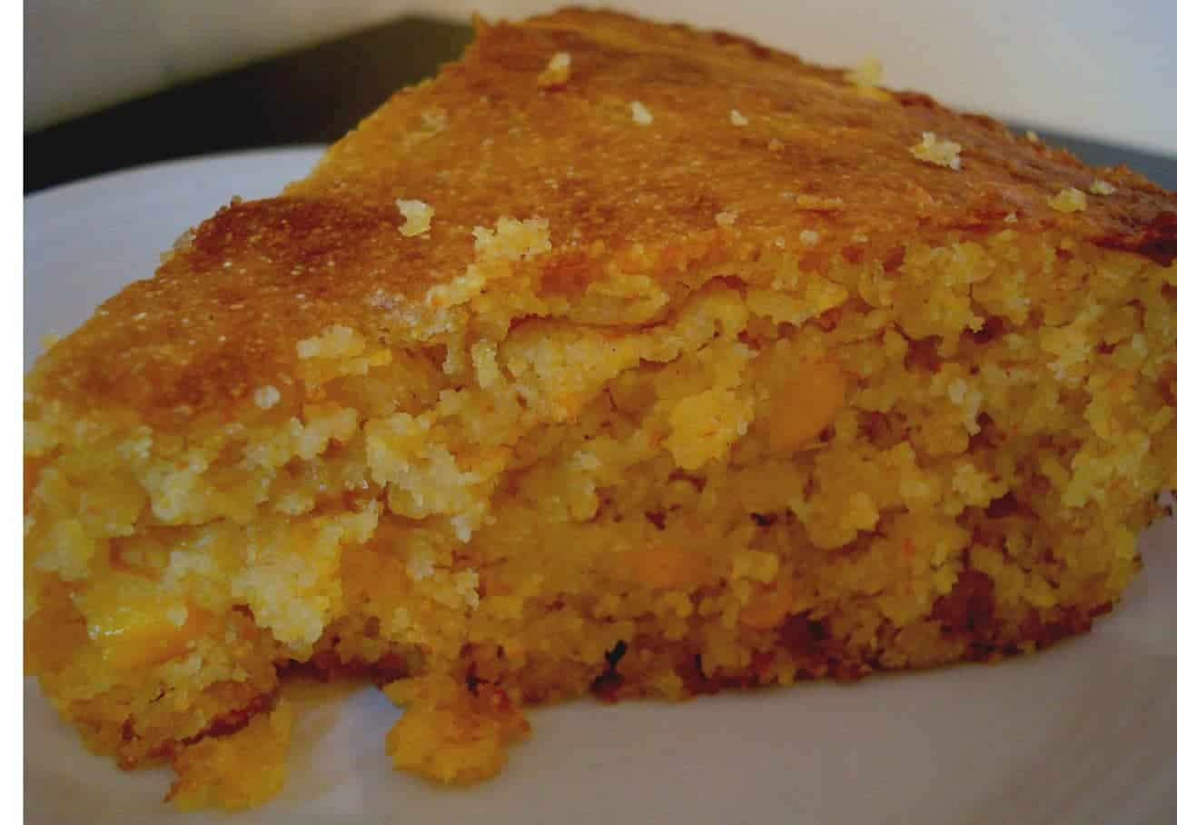 a thick triangle-shaped piece of cornbread on a white plate