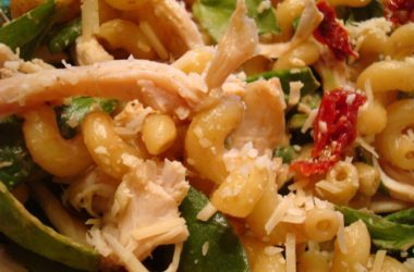 pasta salad with macaroni noodles and spinach and tomatoes mixed in