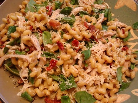 pasta salad with spinach and tomatoes mixed in
