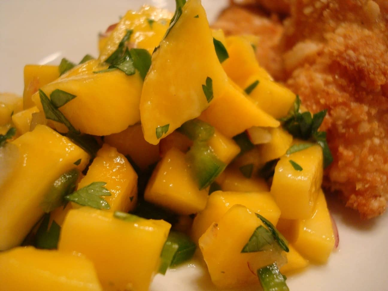 mango salsa and fried chicken on a white plate