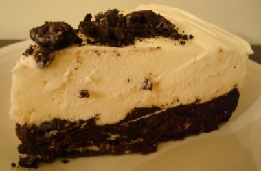 a piece of white chocolate torte with a mousse filling and an oreo crust on a white plate