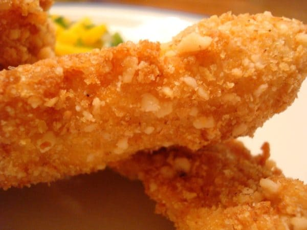 two fried chicken strips on a white plate
