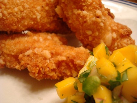 fried macadamia chicken with mango salsa on a white plate
