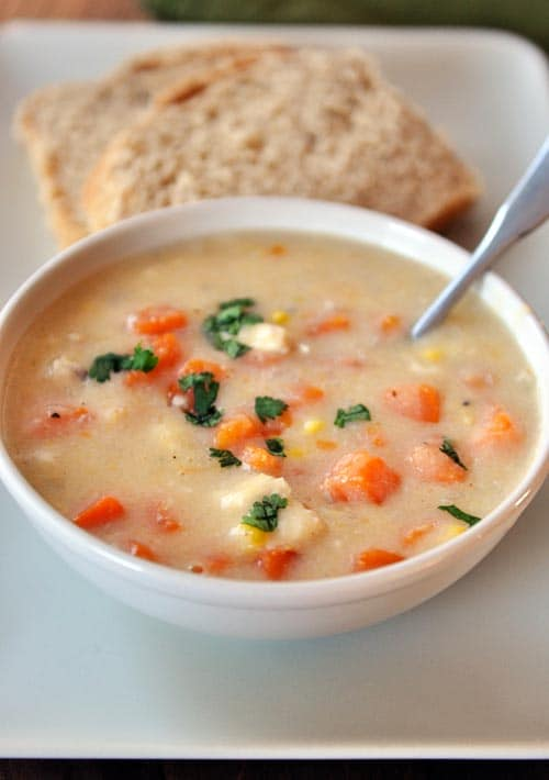 a white bowl of chowder with chunks of chicken, sweet potatoes, and corn