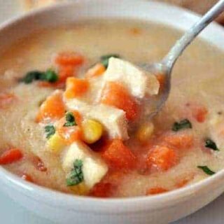 a white bowl of chowder with chicken chunks, sweet potato, and a spoon in it