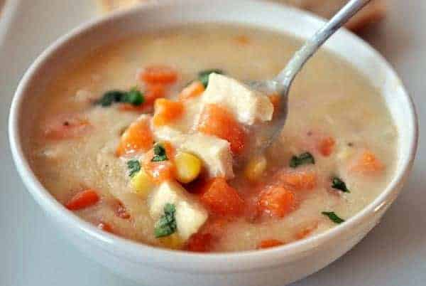 a white bowl of sweet potato chowder with chunks of chicken and a spoon in it
