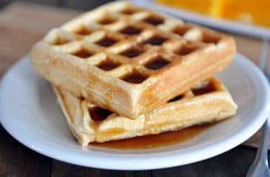 two waffle squares stacked on top of a white plate and covered in syrup
