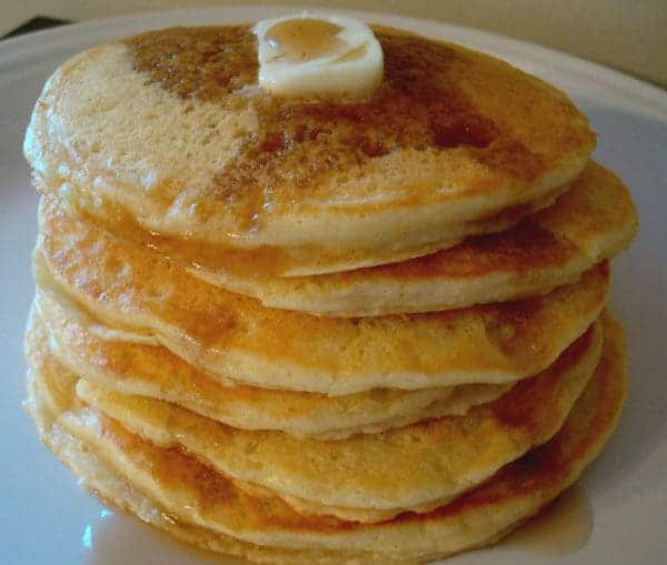 stack of pancakes topped with a pat of butter and syrup on a white plate