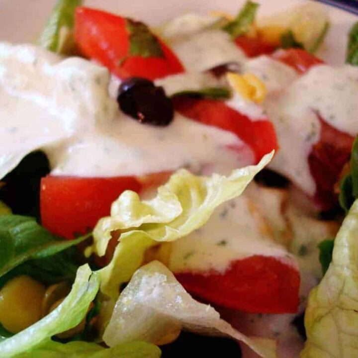 green salad with sliced tomatoes and dressing