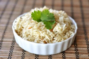 a white ramekin filled with cooked rice and topped with cilantro