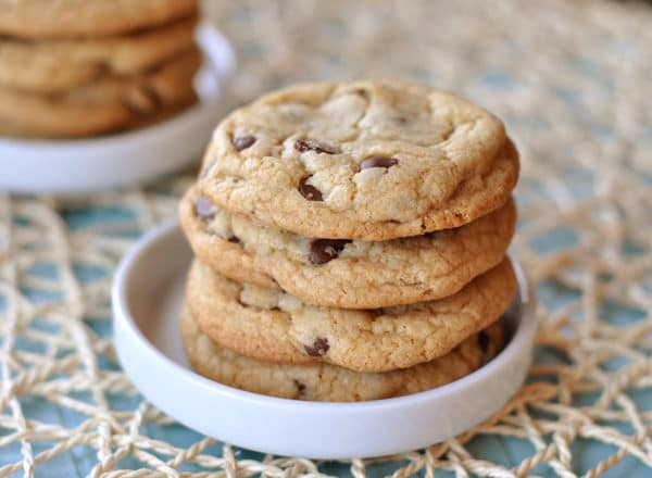 four chocolate chip cookies stacked in a white bowl