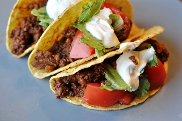 three filled ground beef tacos topped with sour cream lettuce, and tomatoes