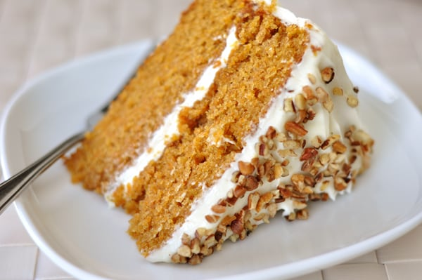 A slice of carrot cake with two layers, white frosting in the middle, and chopped nuts on top on a plate.
