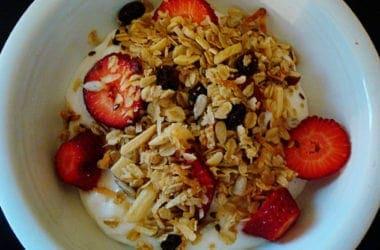granola, strawberries, and yogurt in a white bowl