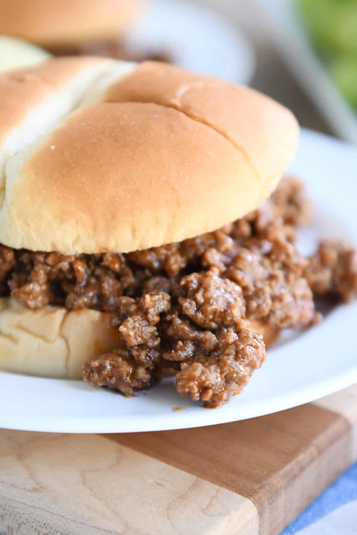 sloppy joe meat spilling over bun onto white plate