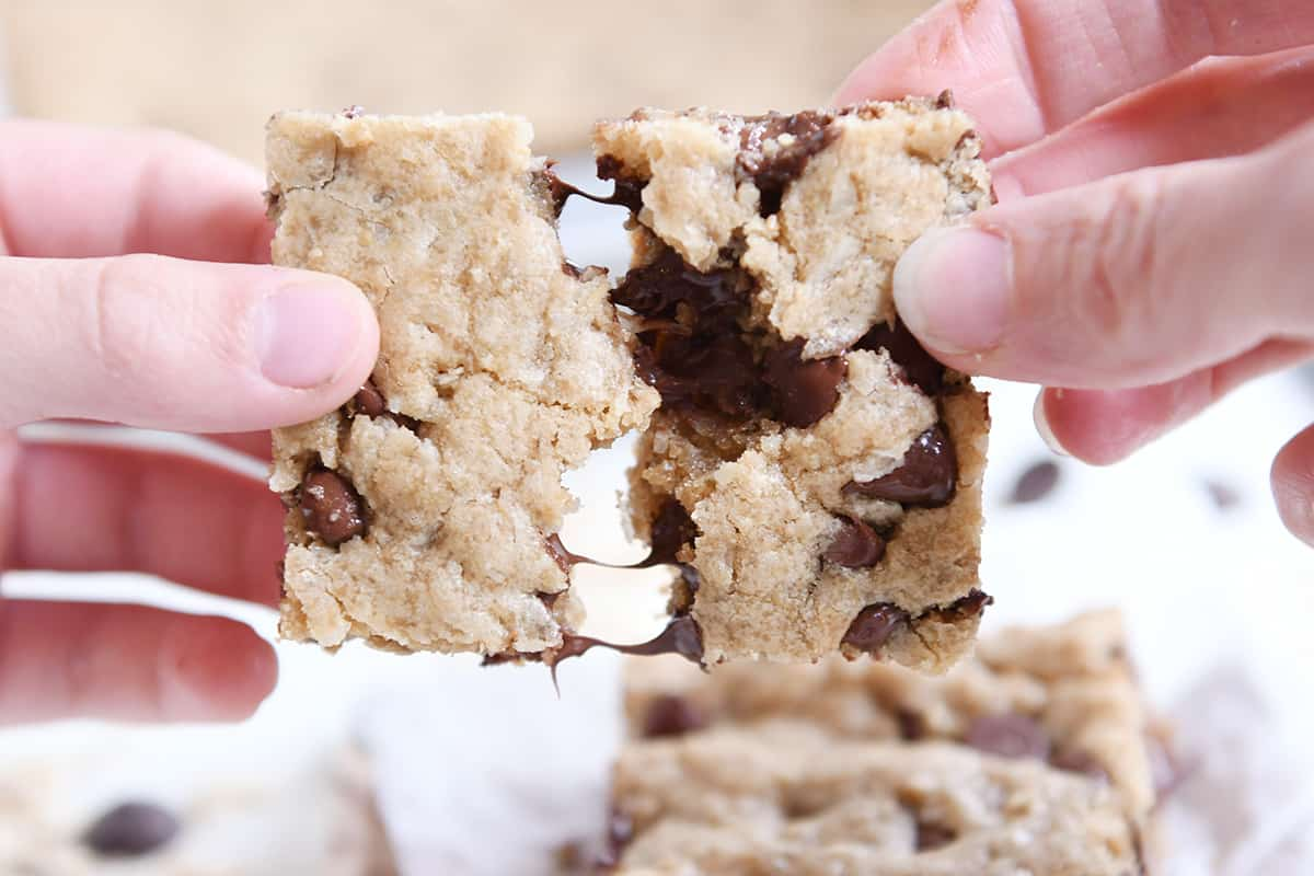 pulling apart two halves of a warm oatmeal chocolate chip coconut cookie bar
