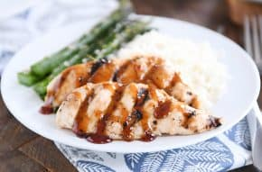 sticky coconut chicken on white plate with coconut rice and asparagus