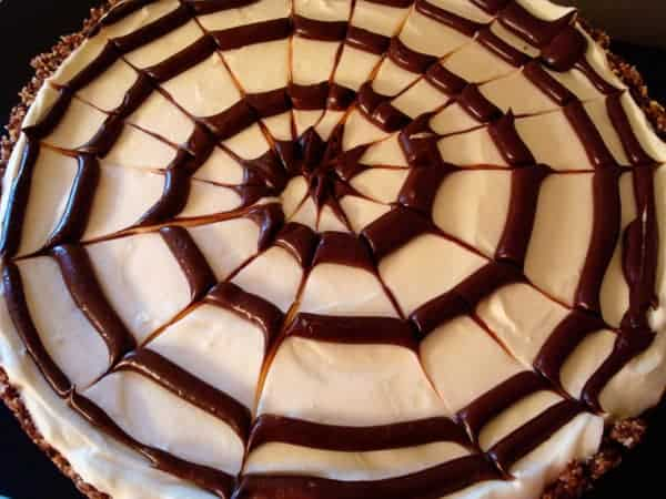 top view of a cheesecake with a spiral chocolate spiderweb on top