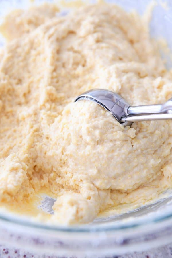 scooping cornbread muffin batter with cookie scoop