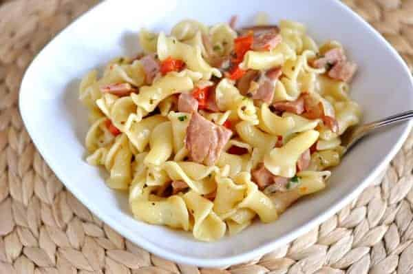 pasta with ham and peppers in a white bowl
