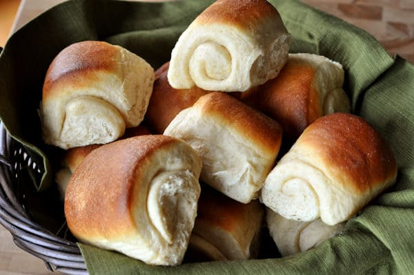 golden brown rolls on a green napkin in a black basket