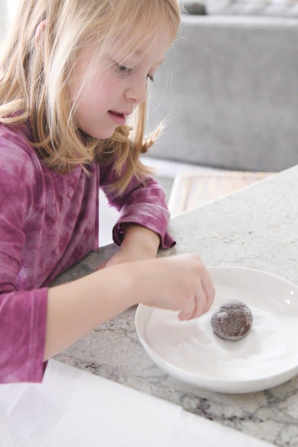 rolling chocolate cookie in granulated sugar