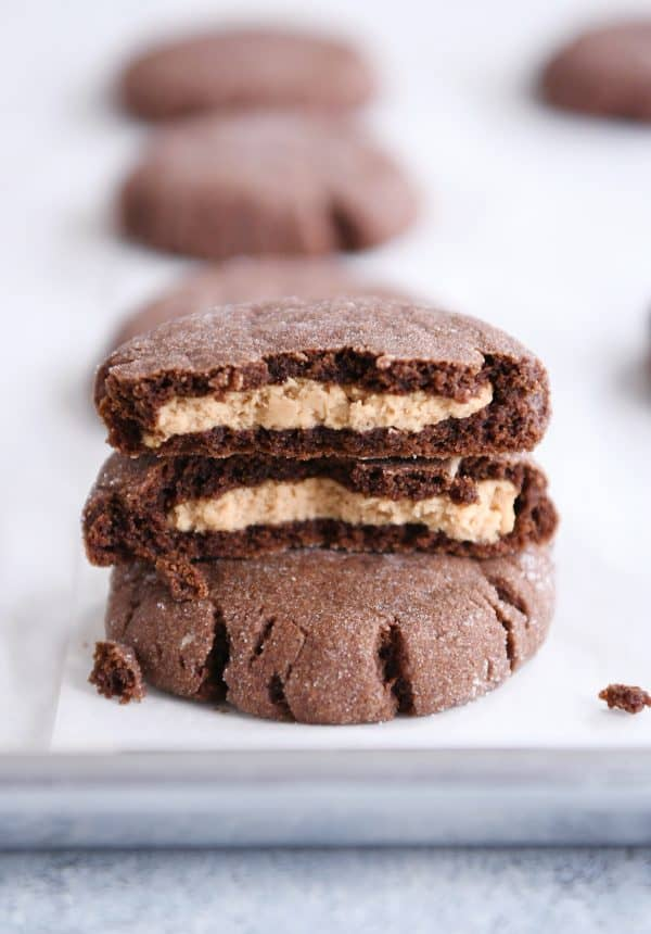 stack of chocolate peanut butter stuffed cookies with top cookie broken in half