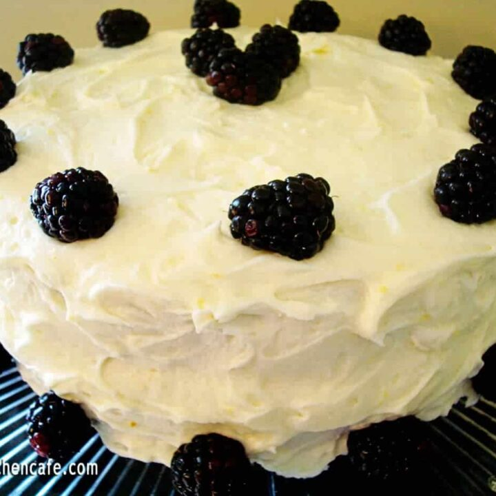 frosted cake with blackberries around the side and top