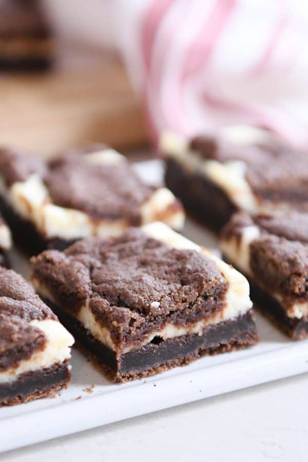 cut squares of black and white cheesecake brownies on white platter