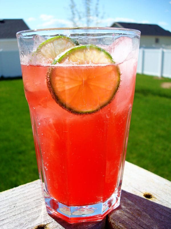 glass filled with raspberry drink, lime, and ice