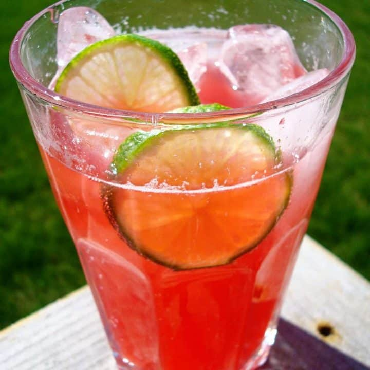 glass cup with raspberry drink and lime slices
