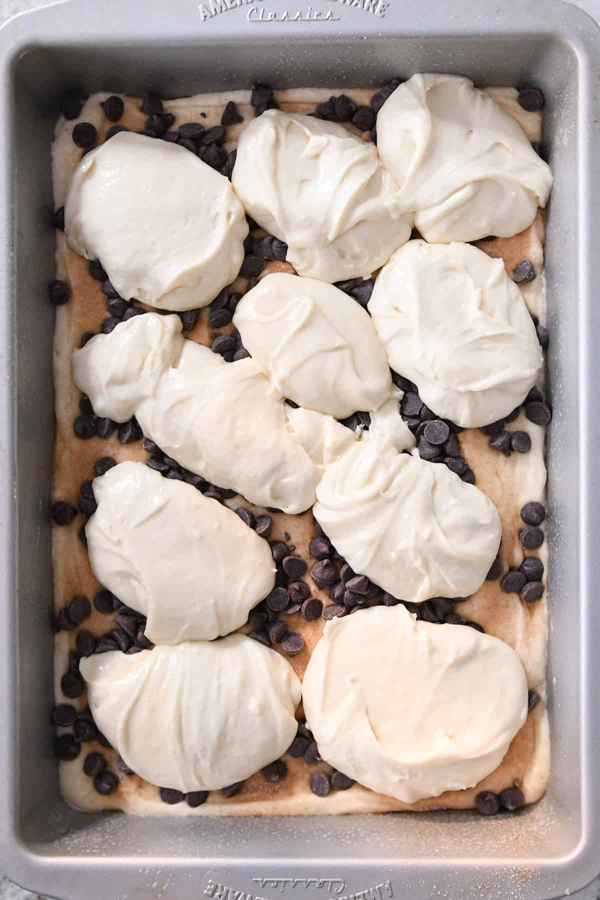 spoonfuls of batter on top of chocolate chips in 9X13-inch pan