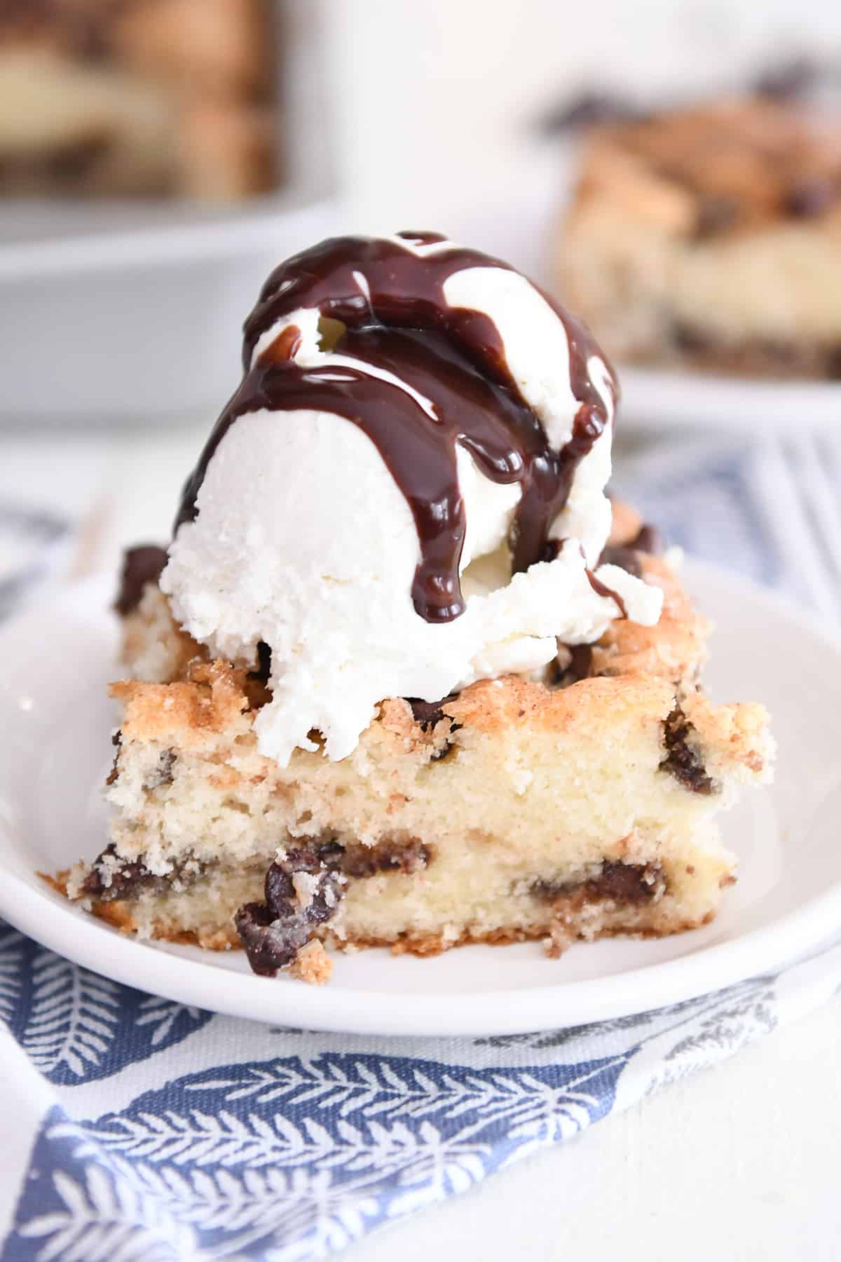 piece of one bowl chocolate chip cake on white plate with ice cream and hot fudge sauce