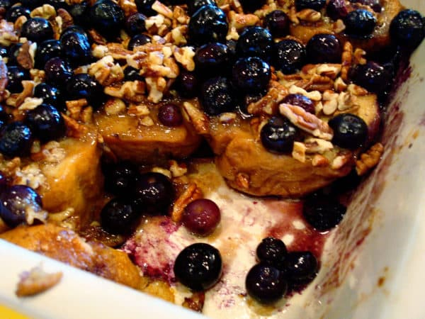 white dish with baked french toast and blueberries with a piece taken out