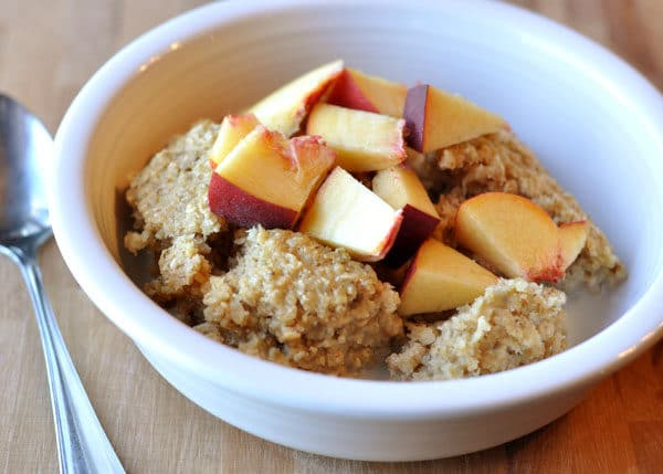 white bowl of oatmeal with fresh peach cut up on top
