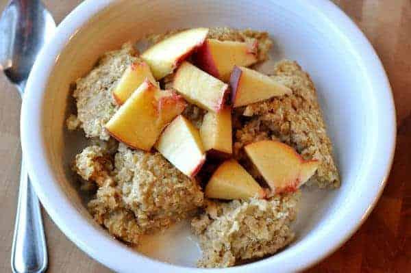 white bowl of baked oatmeal, milk, and fresh peach chunks