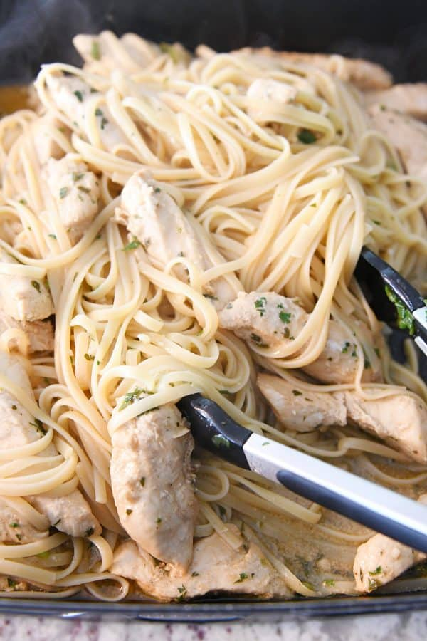 tossing linguine with cooked chicken