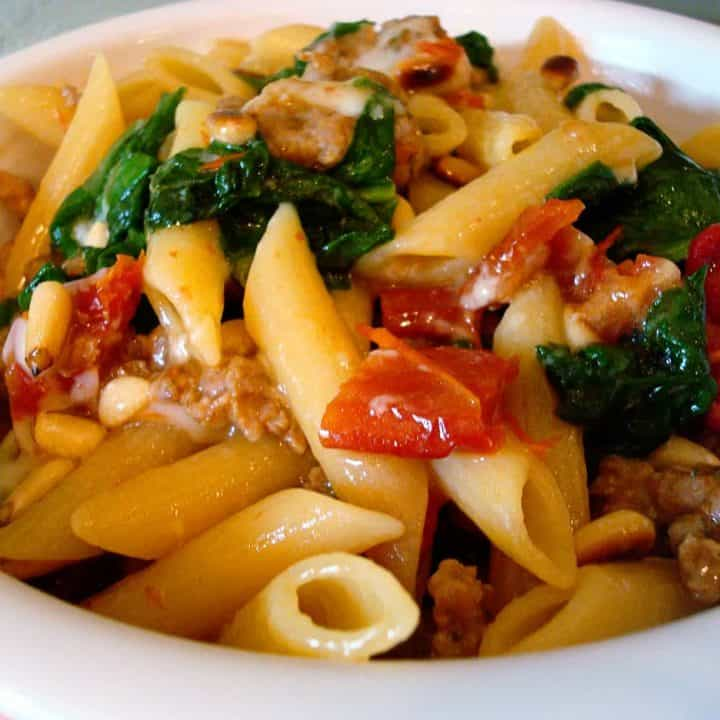 white bowl of pasta, wilted spinach, and tomatoes