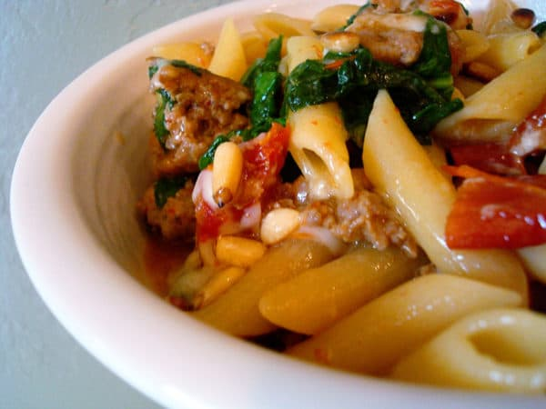 white bowl of pasta, sausage, spinach, and tomatoes