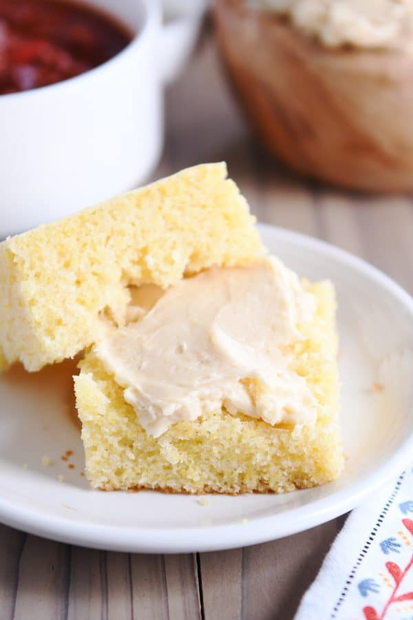 piece of cornbread sliced in half with fluffy honey butter