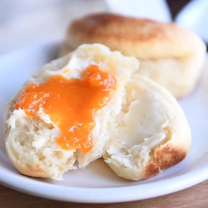 Fluffy Parker house roll in half with butter and apricot jam.