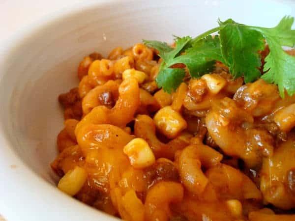 chili pasta with corn and cilantro in a white bowl