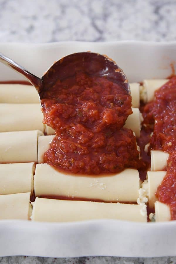 pouring red marinara sauce over rolled manicotti