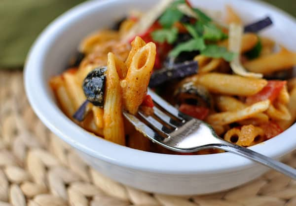 fork with a bite of saucy pasta in a white bowl