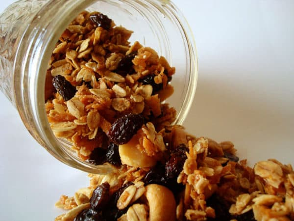 cashew and raisin granola pouring out of a glass mason jar